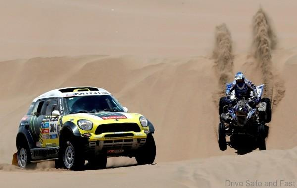 Nani Roma of Spain (L) drives his Mini beside Sergio Lafuente of Uruguay on his Yamaha quad during the ninth stage of the Dakar Rally 2014, from Calama to Iquique, January 14, 2014. REUTERS/Jean-Paul Pelissier (CHILE - Tags: SPORT MOTORSPORT)