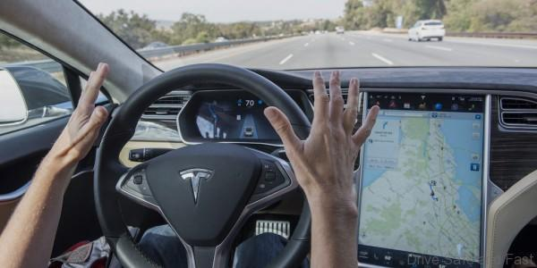 "A member of the media test drives a Tesla Motors Inc., Model S car equipped with Autopilot at the Tesla Motors Inc. headquarters in Palo Alto, California, U.S., on Wednesday, Oct. 14, 2015. Tesla Motors Inc. will begin rolling out the first version of its highly anticipated ""autopilot"" features to owners of its all-electric Model S sedan Thursday. Autopilot is a step toward the vision of autonomous or self-driving cars, and includes features like automatic lane changing and the ability of the Model S to parallel park for you. Photographer: David Paul Morris/Bloomberg"